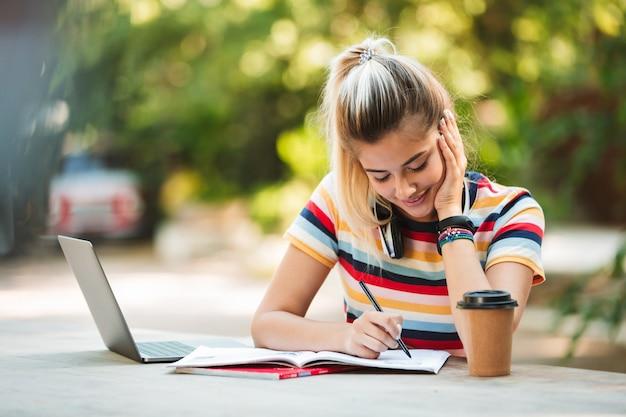 ラップトップコンピューターを使用して公園に座っている幸せな若いかわいい女の子の学生。