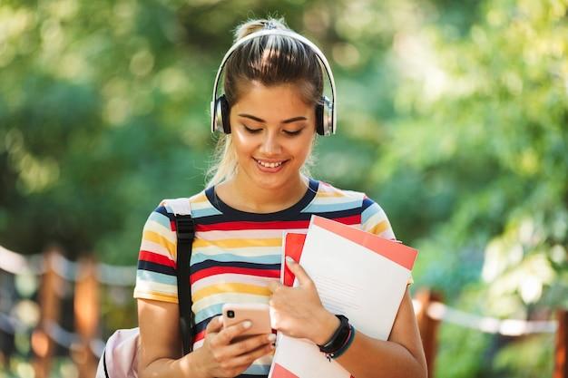 Счастливый молодой симпатичный студент девушки гуляя в парке с рюкзаком, используя музыку мобильного телефона слушая.