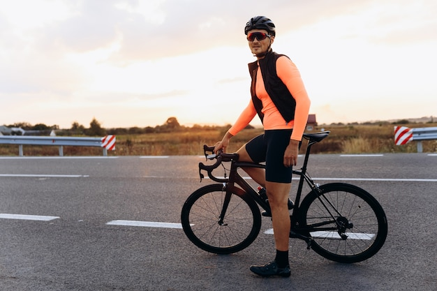 Happy young cyclist dressed in sport clothing posing with black bike on paved road