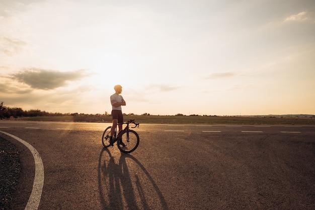 자전거 도로에 서서 신선한 공기에 아름다운 일몰을 즐기는 행복한 젊은 사이클