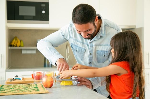 幸せな若いお父さんと娘が一緒に料理を楽しんでいます。少女と彼女の父親は、台所のカウンターでレモンジュースを絞っています。家族の料理のコンセプト