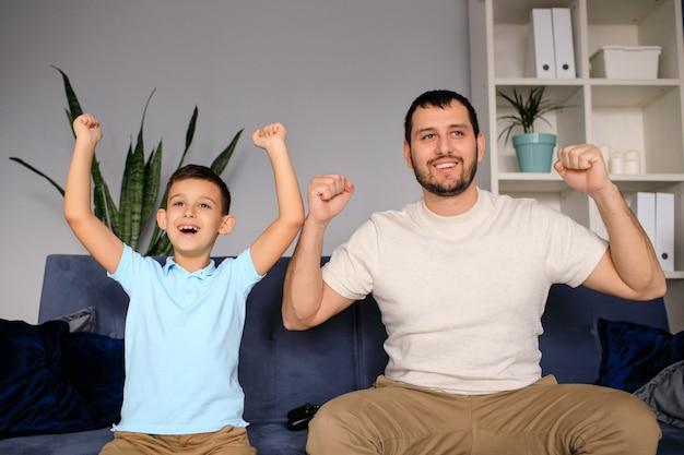 Счастливый молодой папа и сын, сидя на диване в гостиной, играя в компьютерную видеоигру