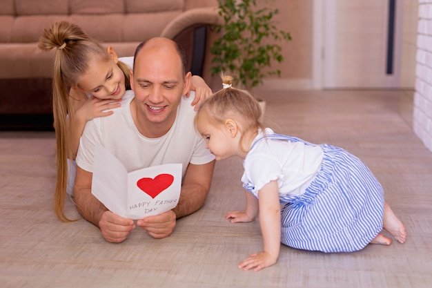 Happy young dad holds a card from little cheerful daughters on fathers day during home holiday