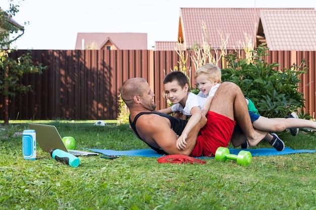 행복 한 젊은 아빠는 녹색 잔디에 그녀의 아기와 함께 놀고 있다. 행복 한 가족의 개념입니다. 아버지의 날. 아빠와 아들은 휴일에 뒤뜰에서 함께 활동합니다.