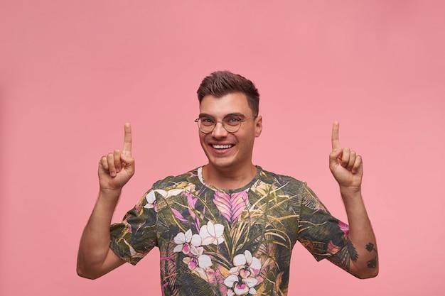 上げられた手で笑って、指を上に向けて、立っているカジュアルなtシャツで幸せな若い黒髪の男