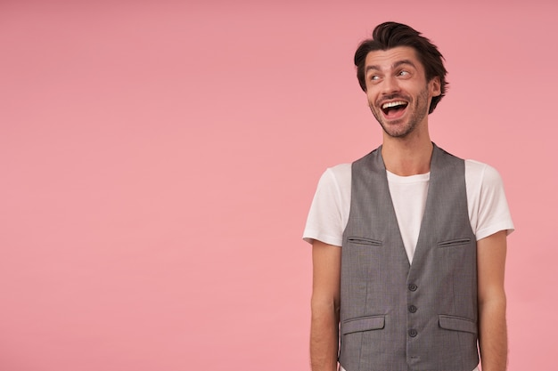 Happy young dark haired man wearing grey waistcoat and white t-shirt, standing with hands down, looking aside with wide smile, positive emotions concept
