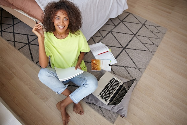 Happy young dark skinned curly woman making notes in her notebook, looking with charming smile, sitting on carpet with geometric print