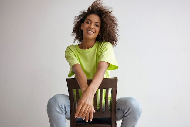 Happy young dark skinned female posing with wild curly hair, sitting on chair with crossed hands and smiling widely