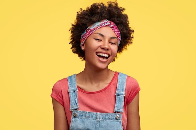 カジュアルな服を着て、家事を終えることを喜んで、黄色い壁の上に隔離された、歯を見せる笑顔を持っている、アフロの髪型の幸せな若い暗い肌の女性。ポジティブな感情の概念