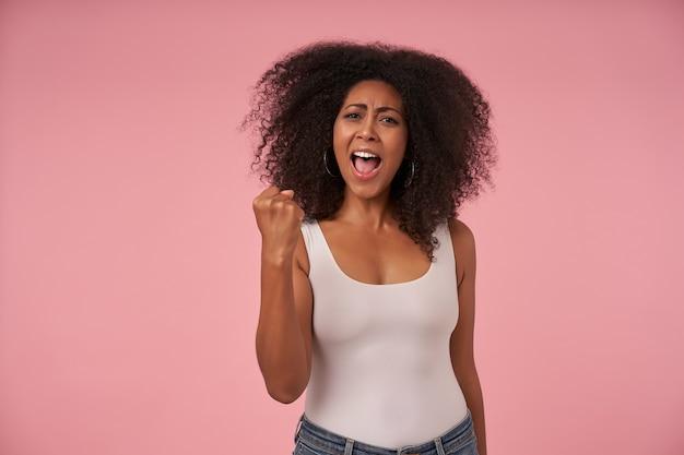 カジュアルな服を着て、巻き毛の髪型でカジュアルな幸せな若い暗い肌の女性、ピンクで隔離、広い口を開いて喜んで拳を上げる
