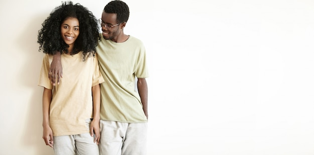 幸せな若い浅黒い肌の男性と女性がカジュアルな服を着てお互いをハグし、家で一緒に楽しい時間を過ごす