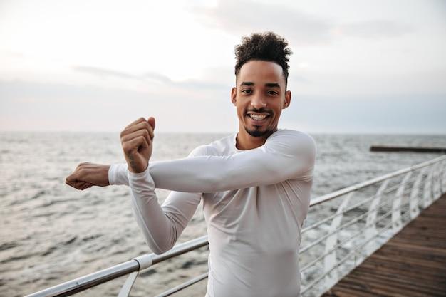 白いスポーツシャツを着た幸せな若い浅黒い肌の男が伸びて腕の運動をします