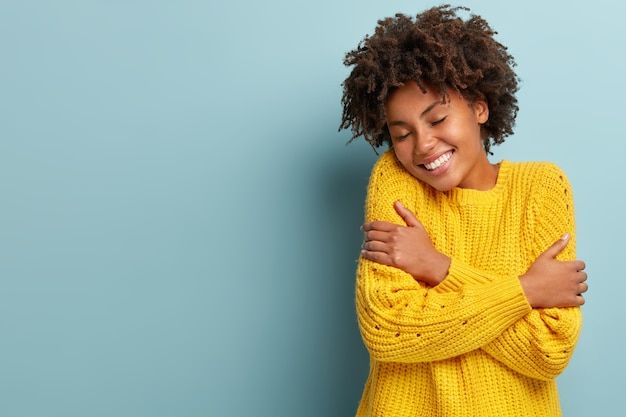 Happy young dark skinned woman hugs herself, feels warmth cozy, wears yellow knitted sweater