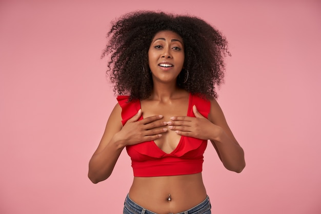 Happy young dark skinned woman with belly button piercing keeping palms on her breast and with pleased broad smile, posing on pink in casual clothes