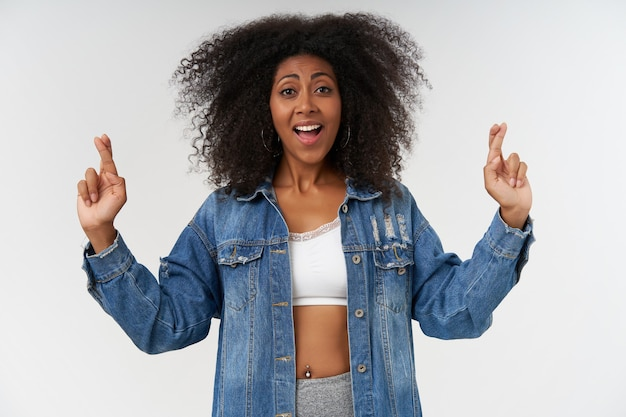 幸運のために人差し指を交差させる巻き毛を持つ幸せな若い暗い肌の女性、広い喜びの笑顔で、白いトップとジーンズのコートの白い壁の上に立っています