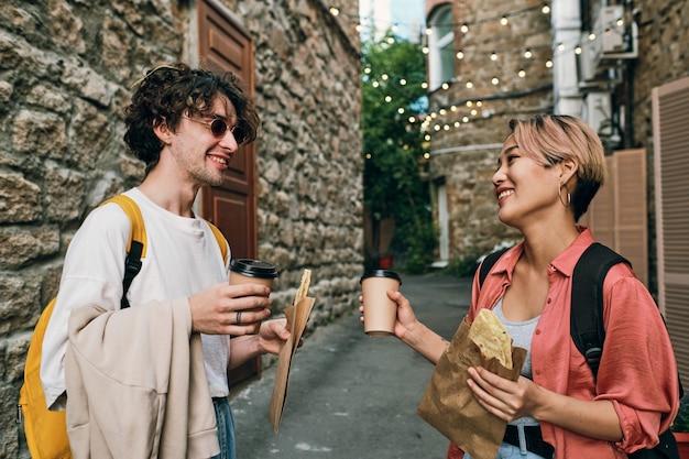 お互いを見つめている飲み物と軽食で幸せな若いデート