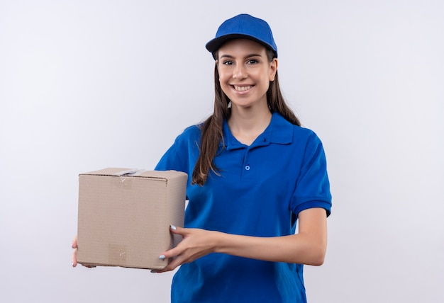 Felice giovane ragazza di consegna in uniforme blu e berretto tenendo il pacchetto scatola sorridente fiducioso