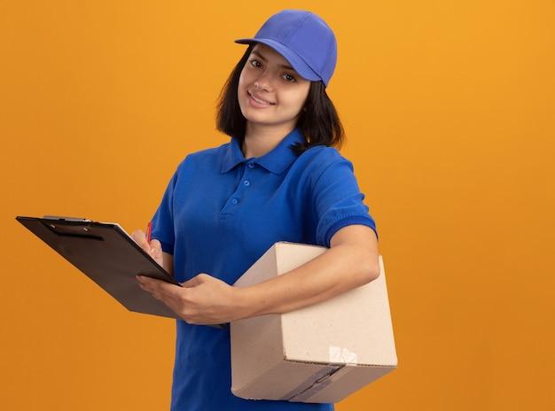 Felice giovane ragazza di consegna in uniforme blu e cappuccio tenendo la scatola di cartone e appunti guardando con il sorriso sul viso in piedi sopra la parete arancione