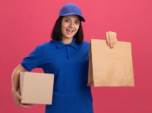 Felice giovane ragazza delle consegne in uniforme blu e cappuccio che tiene il pacchetto di carta e la scatola di cartone sorridendo allegramente in piedi sopra la parete rosa