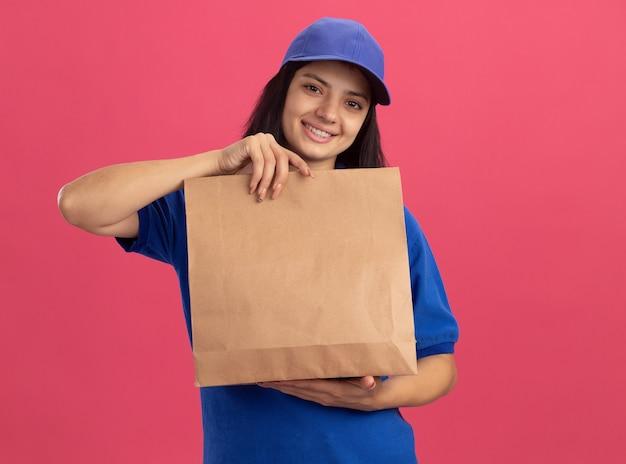 Счастливая молодая доставщица в синей форме и кепке показывает бумажный пакет, весело улыбаясь, стоя над розовой стеной