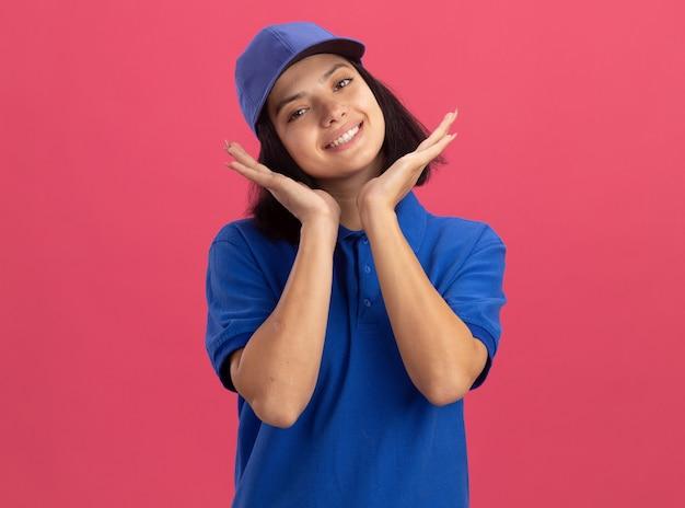 Счастливая молодая доставщица в синей форме и кепке, широко улыбаясь, стоя над розовой стеной