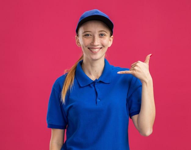 Счастливая молодая доставщица в синей униформе и кепке, уверенно улыбаясь, делает жест