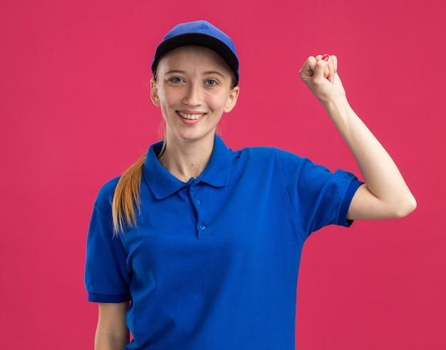 Счастливая молодая доставщица в синей форме и кепке улыбается, уверенно поднимая кулак, стоя над розовой стеной