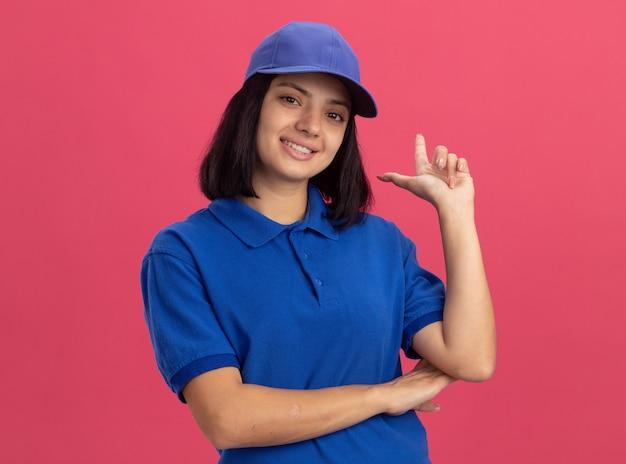Счастливая молодая доставщица в синей униформе и кепке, улыбаясь, указывая пальцем вверх, стоя над розовой стеной