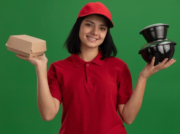 緑の壁の上に立ってフレンドリーな笑顔の食品パッケージと帽子を保持している赤い制服を着た幸せな若い配達の女の子