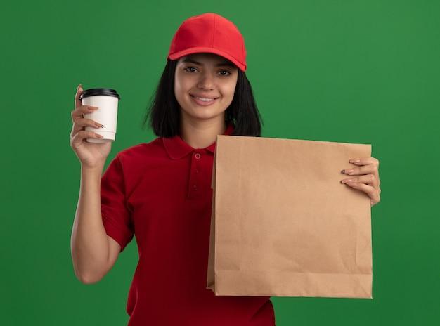 Счастливая молодая доставщица в красной форме и кепке, держащая бумажный пакет и чашку, весело улыбаясь, стоя над зеленой стеной