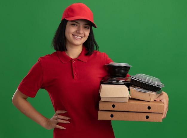 Счастливая молодая доставщица в красной форме и кепке держит коробки для пиццы и продуктовые пакеты, весело улыбаясь, стоя над зеленой стеной
