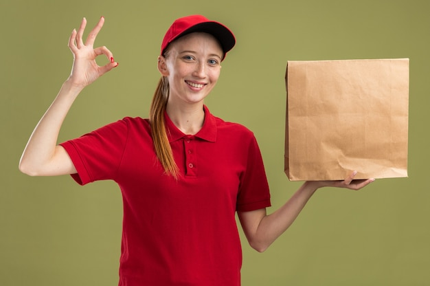 Happy young delivery girl in red uniform and cap holding package   smiling confident doing ok sign