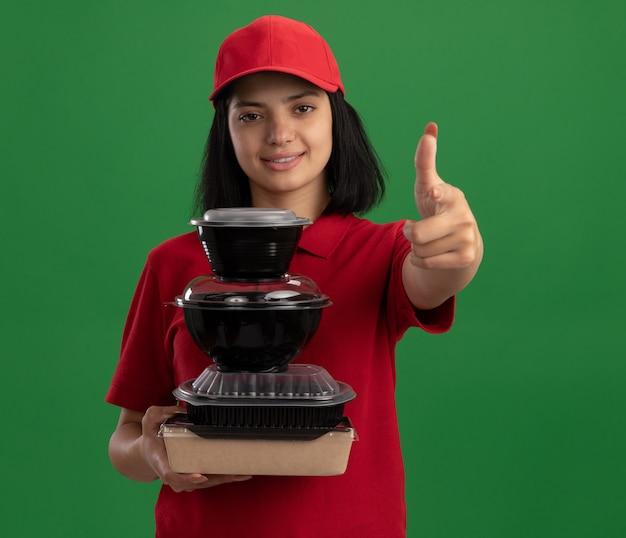 Felice giovane ragazza di consegna in uniforme rossa e cappuccio che tiene pila di confezioni di cibo sorridente amichevole che mostra i pollici in su in piedi sopra la parete verde