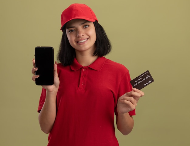 Happy young delivery girl in red uniform and cap showing smartphine and credit card  smiling cheerfully standing over green wall