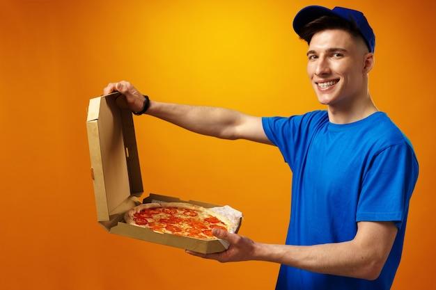黄色の背景にピザボックスを保持している幸せな若い配達人