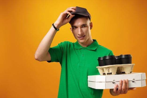 黄色の表面に対してピザボックスを保持している幸せな若い配達人