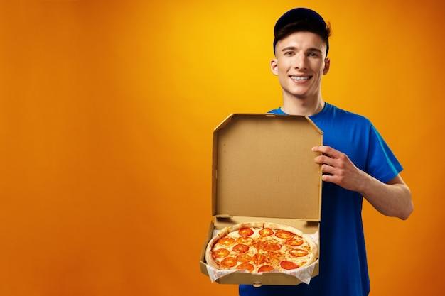 黄色に対してピザボックスを保持している幸せな若い配達人