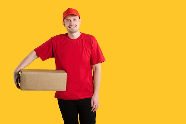 赤い制服を着た幸せな若い配達人は、カートンボックスと黄色に立っています
