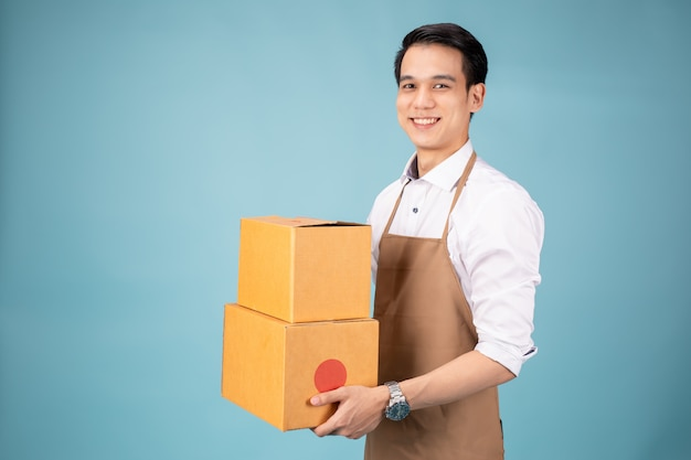 Happy young delivery man standing with parcel post box
