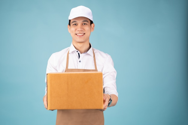 Happy young delivery man in white cap standing with parcel post box