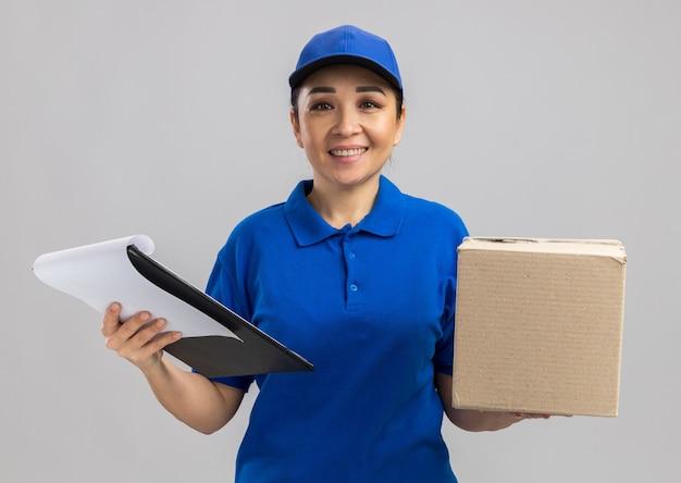 Felice giovane donna delle consegne in uniforme blu e cappuccio con scatola di cartone e appunti con un sorriso sul viso in piedi su un muro bianco