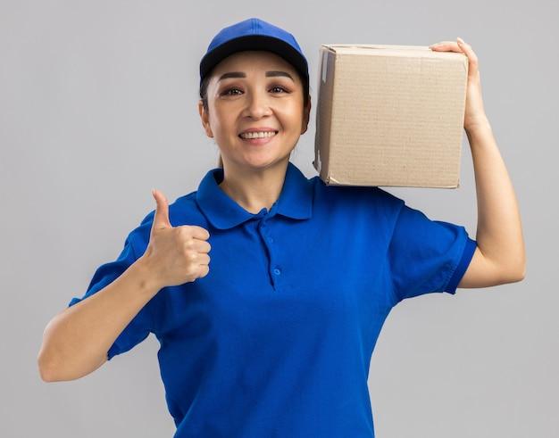 Felice giovane donna delle consegne in uniforme blu e cappuccio che tiene in mano una scatola di cartone con un sorriso sul viso che mostra i pollici in su