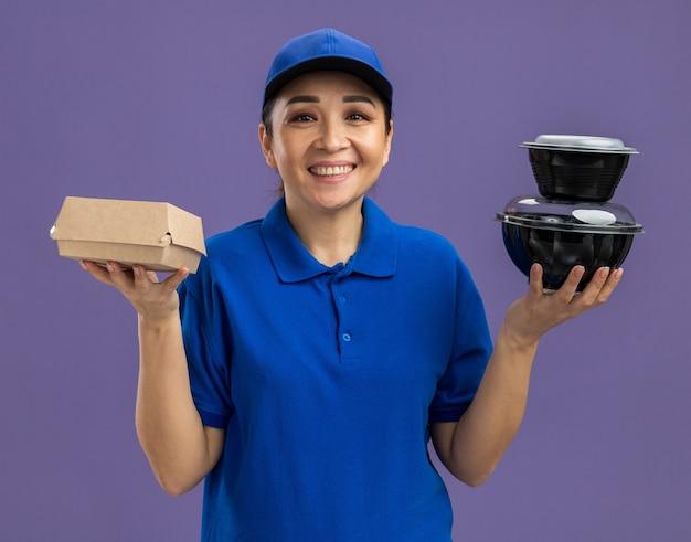 Felice giovane donna delle consegne in uniforme blu e berretto che tiene in mano pacchi di cibo sorridendo allegramente in piedi sul muro viola