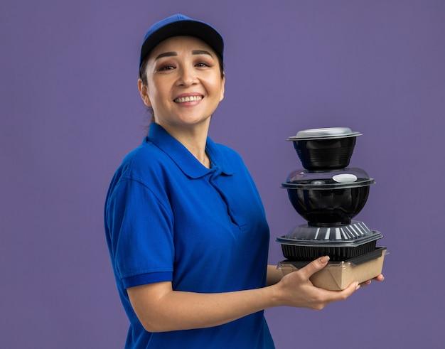 Felice giovane donna delle consegne in uniforme blu e berretto che tiene in mano confezioni di cibo sorridenti allegramente