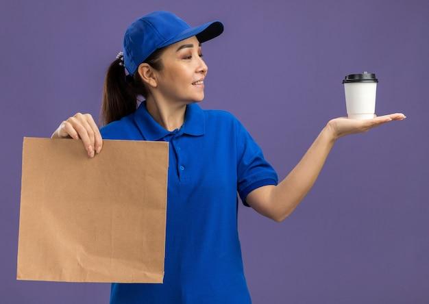 Felice giovane donna delle consegne in uniforme blu e berretto che tiene in mano un pacchetto di carta che presenta un bicchiere di carta che sembra fiducioso sorridente in piedi sul muro viola