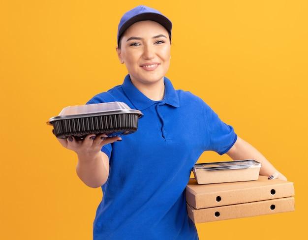 Felice giovane donna delle consegne in uniforme blu e cappuccio tenendo scatole per pizza e confezioni di cibo guardando davanti sorridente fiducioso in piedi sopra la parete arancione