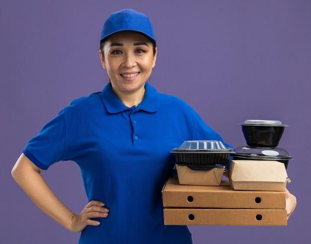 Felice giovane donna delle consegne in uniforme blu e berretto che tiene scatole per pizza e confezioni di cibo sorridenti allegramente in piedi sul muro viola