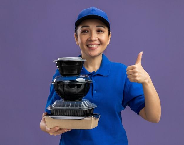 Felice giovane donna delle consegne in uniforme blu e berretto che tiene una pila di pacchi di cibo sorridendo allegramente mostrando i pollici in piedi sul muro viola purple