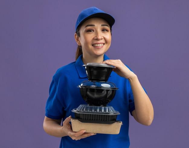 Felice giovane donna delle consegne in uniforme blu e berretto che tiene una pila di confezioni di cibo sorridendo allegramente