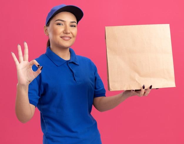 파란색 제복을 입은 행복 한 젊은 배달 여자와 분홍색 벽 위에 서있는 확인 서명을 유쾌하게 보여주는 전면을보고 종이 패키지를 들고 모자